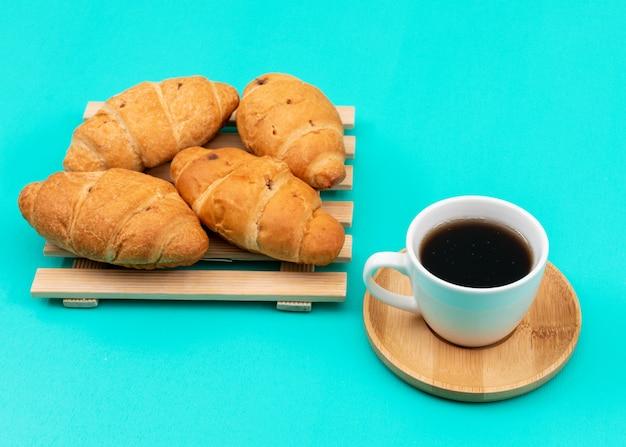 Boczny widok croissants z kawą na błękit powierzchni ukazuje się horyzontalnie