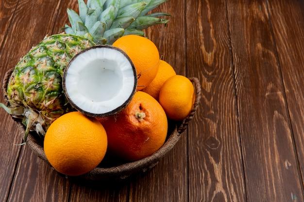 Boczny widok cytrus owoc jako ananasowy kokosowy pomarańczowy tangerine w koszu na drewnianym tle z kopii przestrzenią