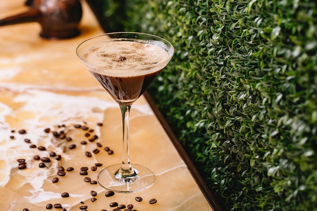 Boczny widok czekoladowy martini z pikantność cynamonem w szklanych i kawowych fasolach na stole