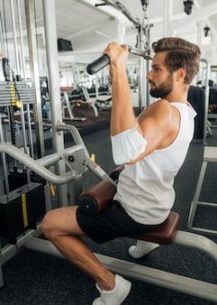 Boczny widok człowieka z maską medyczną na przedramieniu, ćwicząc na siłowni
