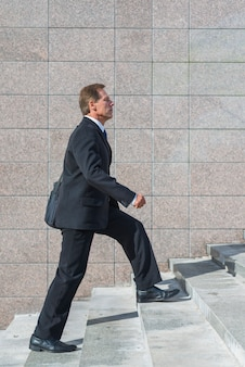 Boczny widok dojrzałego biznesmena wspinaczkowy schody