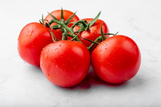 Boczny widok dojrzali świezi pomidory z wodą opuszcza na białym tle