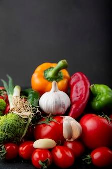 Boczny widok dojrzałych świeżych warzyw kolorowych dzwonkowych pieprzy pomidorów czosnku brokuły i zielona cebula na czarnym tle