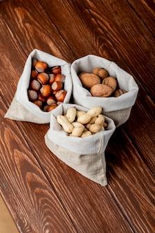 Boczny widok dokrętki w worków orzechów włoskich arachidach i hazelnuts w skorupie na drewnianym tle