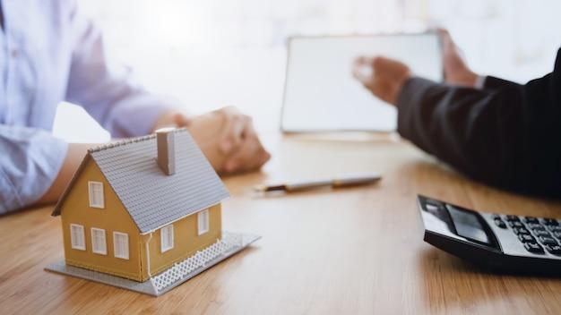 Boczny widok domowy pożyczkowy agent trzyma pustego ekranu pastylkę przedstawia klient