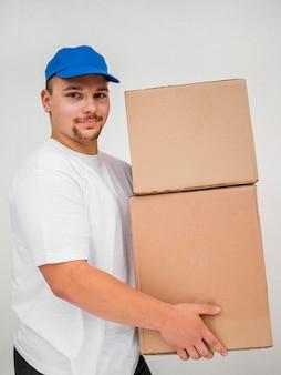 Boczny widok doręczeniowego mężczyzna mienia pudełka