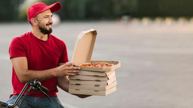 Boczny widok doręczeniowy facet z motocyklem i pizzą