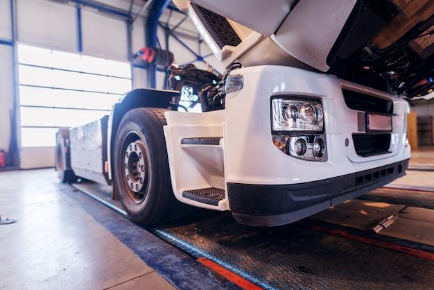 Boczny widok duża ciężarówka w samochodowym warsztacie. naprawianie starej ciężarówki lub tworzenie nowej w warsztacie.