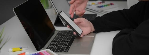 Boczny widok dwa bizneswoman konsultuje na ich pracie z egzaminu próbnego smartphone