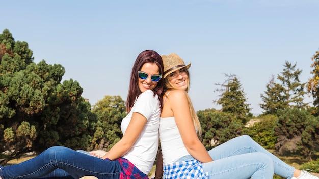 Boczny widok dwa szczęśliwego żeńskiego przyjaciela siedzi z powrotem popierać