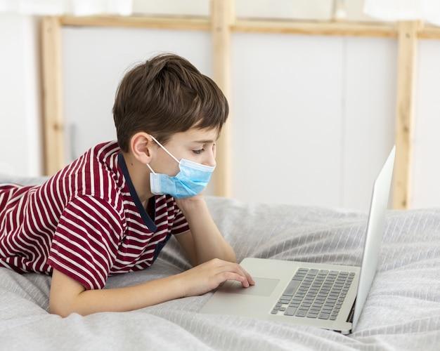 Boczny widok dzieciak z medyczną maską bawić się na laptopie