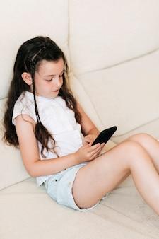 Boczny widok dziewczyny obsiadanie i patrzeć telefon