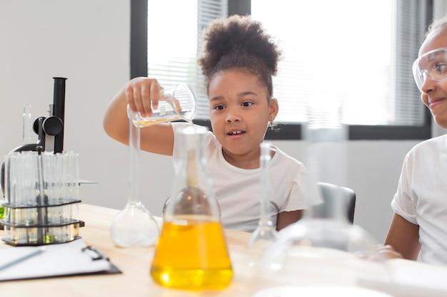 Boczny widok eksperymentuje z chemią dziewczyna naukowiec w domu