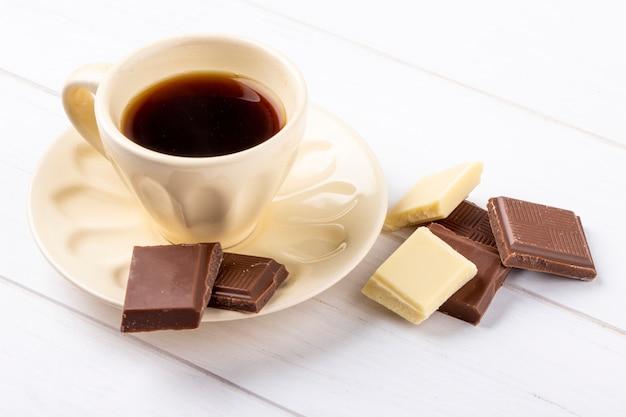 Boczny widok filiżanka kawy z białą i ciemną czekoladą na białym drewnianym tle