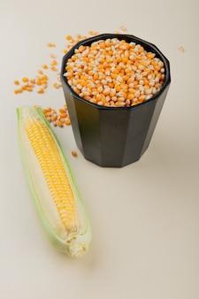 Boczny widok garnek pełno kukurydzani ziarna i kukurudza na bielu stole