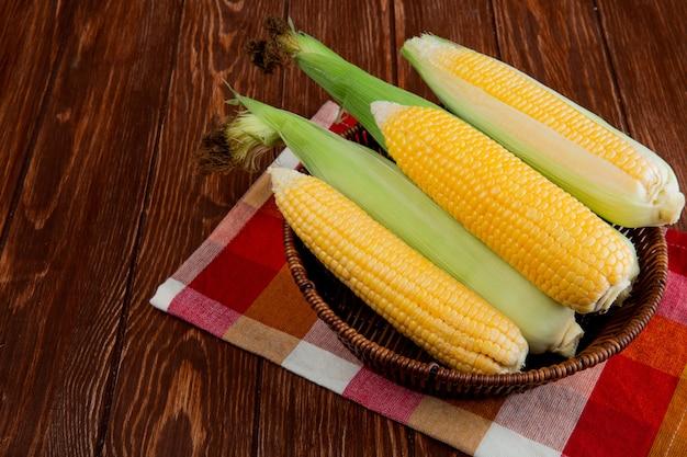 Boczny widok gotować i niegotować kukurudze w koszu na płótnie i drewnianym stole z kopii przestrzenią