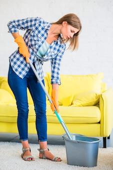 Boczny widok janitor kładzenia kwacz w wiadrze