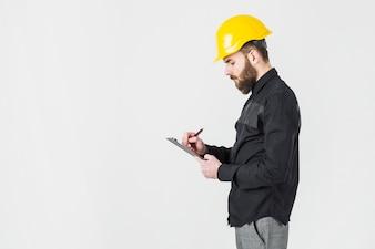 Boczny widok jest ubranym żółtego hardhat writing na schowku męski architekt