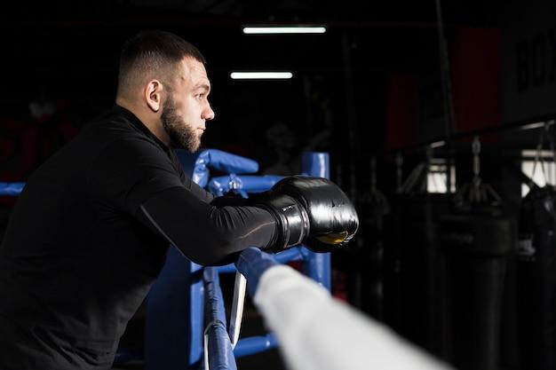 Boczny widok jest ubranym bokserskie rękawiczki mężczyzna