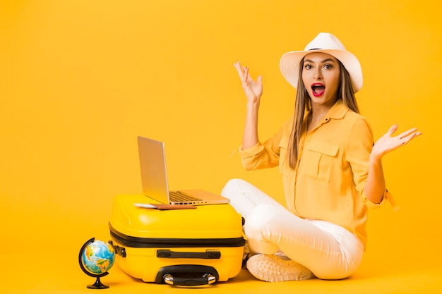 Boczny widok jest ubranym kapelusz zdziwionej kobiety podczas gdy pozujący obok bagażu