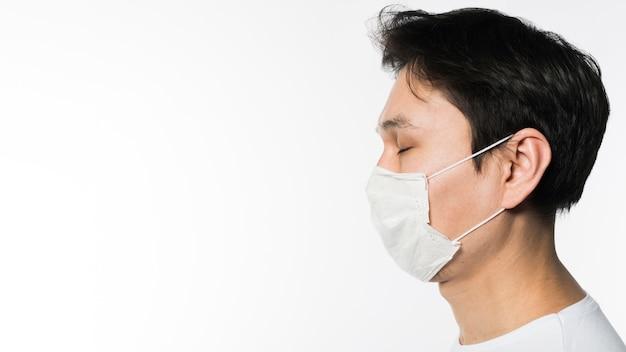Boczny widok jest ubranym medyczną maskę chory mężczyzna