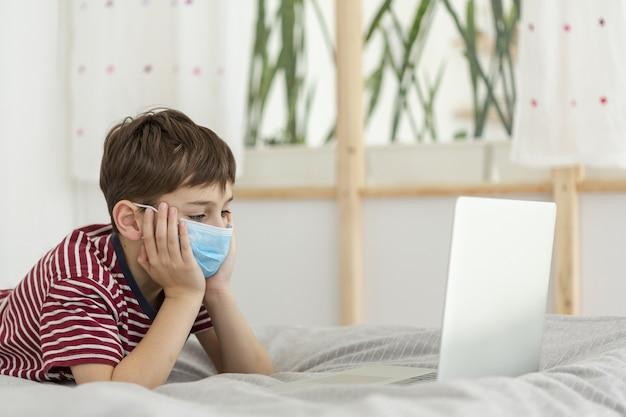 Boczny widok jest ubranym medyczną maskę i patrzeje laptop dziecko