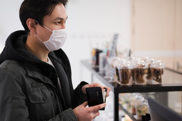 Boczny widok jest ubranym medyczną maskę kupuje coś mężczyzna