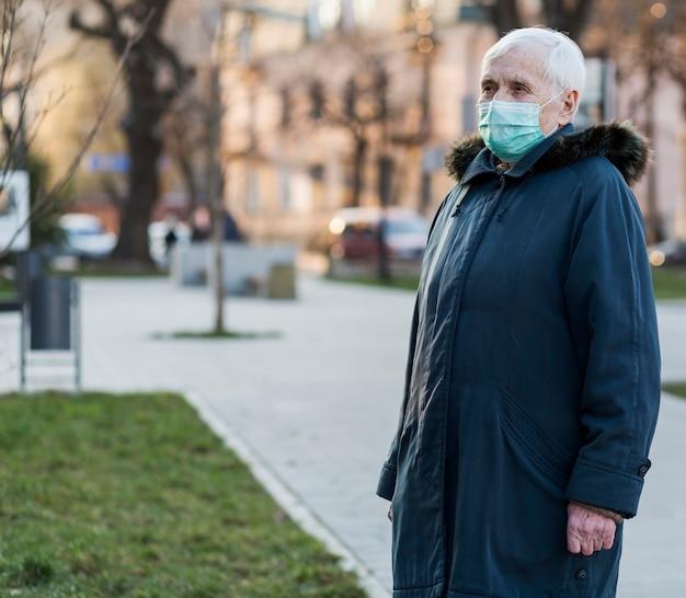 Boczny widok jest ubranym medyczną maskę stara kobieta