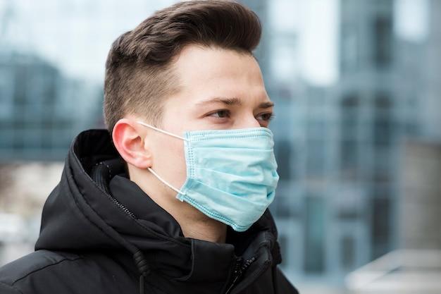 Boczny widok jest ubranym medyczną maskę w mieście mężczyzna
