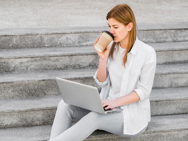 Boczny widok kobieta ma kawę na krokach podczas gdy pracujący na laptopie