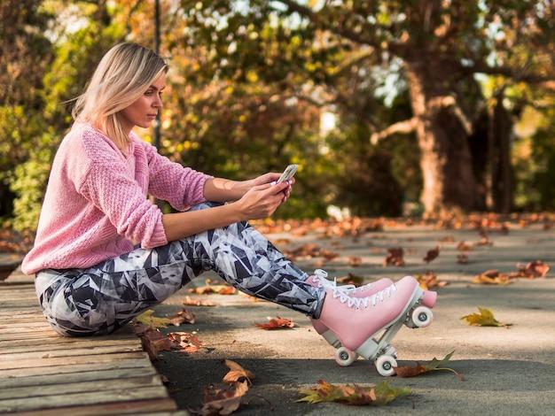 Boczny widok kobieta patrzeje telefon w leginsach