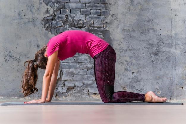 Boczny widok kobieta robi joga ćwiczeniu przeciw popielatej ścianie