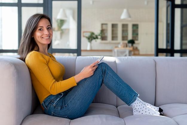 Boczny widok kobieta używa pastylkę na kanapie
