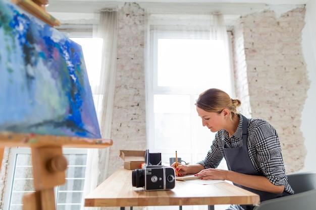 Boczny widok kobieta w fartuchu pracuje przy biurkiem