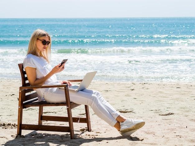 Boczny widok kobieta w plażowym krześle z laptopem i smartphone