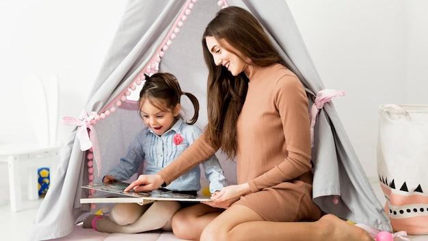 Boczny widok kobieta z młodą dziewczyną bawić się obok namiotu