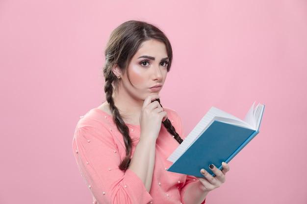 Boczny widok kobiety główkowanie i mienie książka