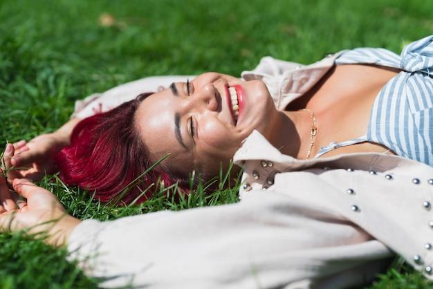 Boczny widok kobiety lying on the beach w trawie