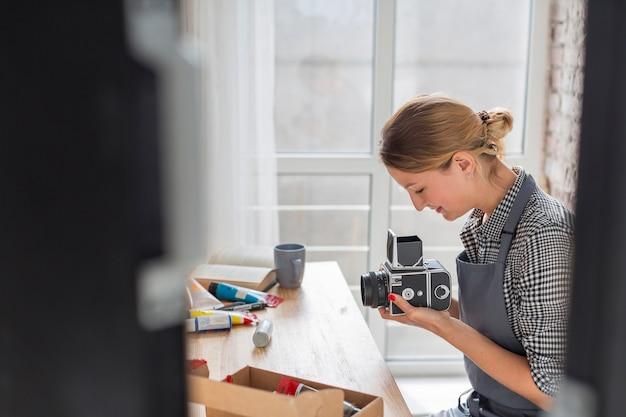 Boczny widok kobiety mienia kamera przy biurkiem