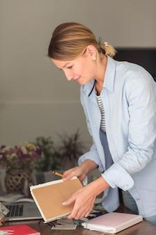 Boczny widok kobiety mienia ołówek i notatnik