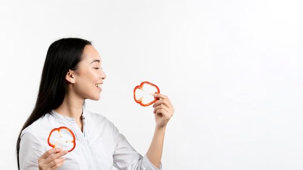 Boczny widok kobiety mienia pieprzu czerwoni plasterki nad białym tłem