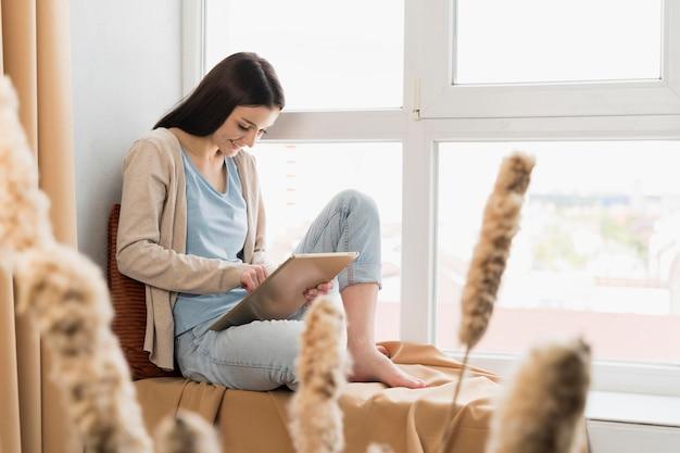 Boczny widok kobiety obsiadanie obok okno i działanie na pastylce
