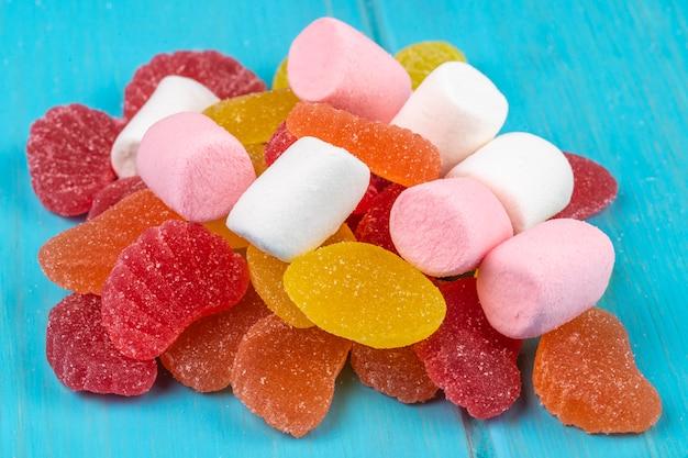 Boczny widok kolorowi smakowici marmoladowi cukierki i marshmallows rozpraszali na błękicie