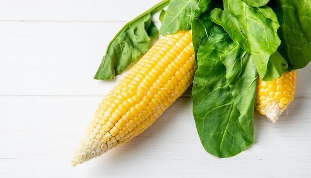 Boczny widok kukurydzany cob i szpinak na drewnianej powierzchni
