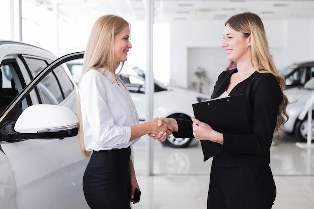 Boczny widok kupuje nowego samochód kobieta