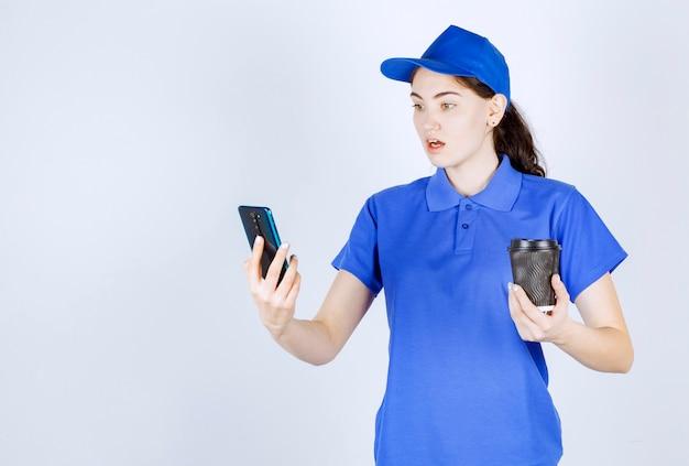 Boczny widok kurierki, która ze zdziwieniem spogląda na swój telefon, trzymając kawę przed białą ścianą