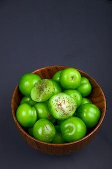 Boczny widok kwaśne zielone śliwki w drewnianym pucharze na czerń stole