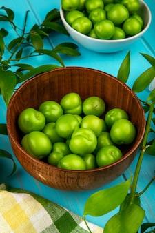 Boczny widok kwaśne zielone śliwki w pucharach na błękitnym drewnianym stole