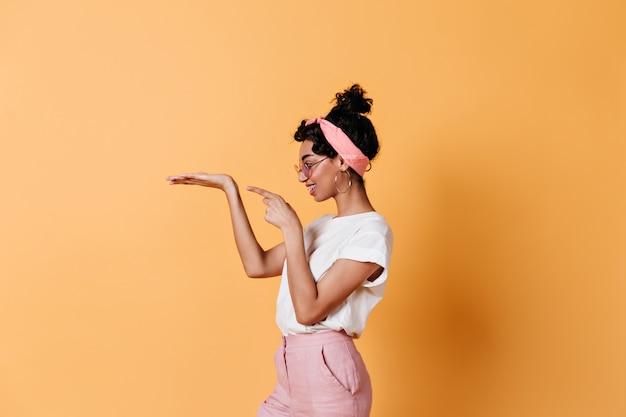 Boczny widok ładna brunetka kobieta gestykuluje na żółtej ścianie