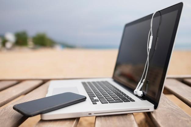 Boczny widok laptop na plażowym krześle z smartphone